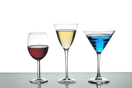 Red wine, white wine and a blue martini in glasses on a reflective silver table with a white background. photo