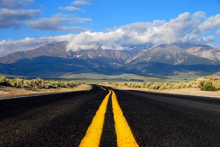 road marking: Road leads to cloud covered mountains in the summer. Middle of the road life.