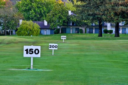 driving range: Yardage signs mark the distance on a golf  driving range