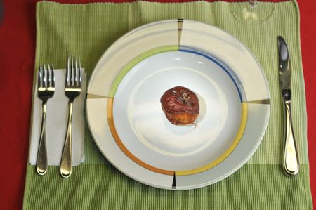 A nice placesetting with a plate with a rotten apple.