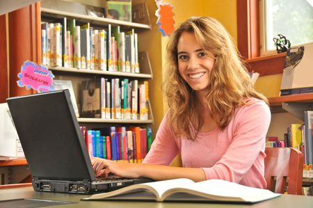 Young woman typing on a laptop in the library with an open book