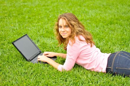 Young woman typing on a laptop ouside on the grass photo