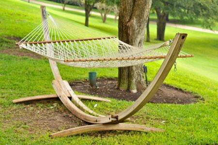 An empty hammock on grass by trees on a hill