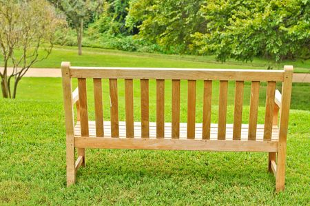 Empty wood bench on grass overlooking a path Imagens