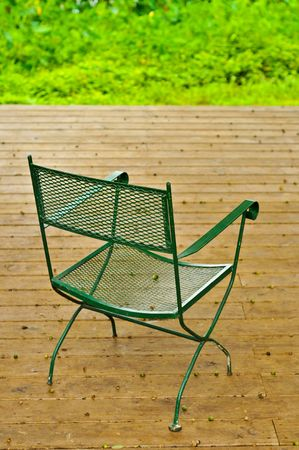An empty chair sits on a wooden deck with acorns