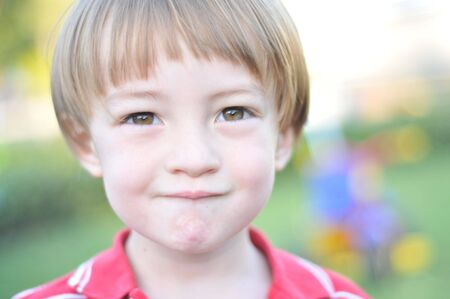 Boy looks at the camera biting his lip with narrow depth of field Фото со стока