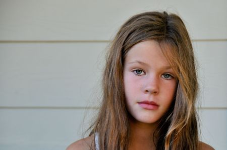 A young girl with brown hair looks at the camera.