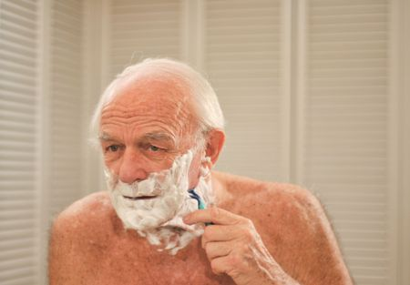 Elderly man shaves in front of a mirror.