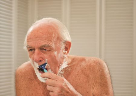 shaving cream: Elderly man shaves in front of a mirror.