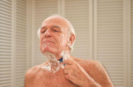 Oudere man scheert voor een spiegel. Stockfoto