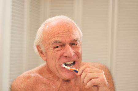 Elderly man brushes his teeth  in front of a mirror.