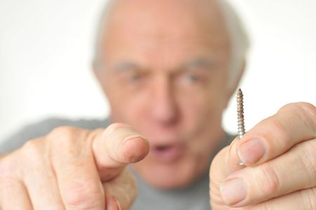 Man points to camera holding a screw.