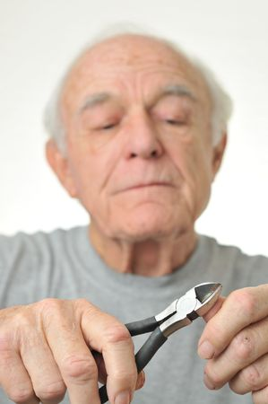Man cuts his fingernails with plyers. Stock Photo