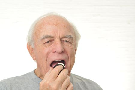 Man eats the cream from the inside of a filled cookie. Stock Photo