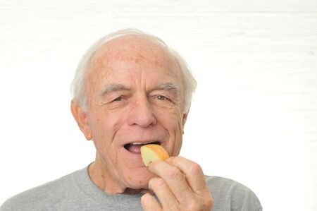 A happy man eats a slice of apple.