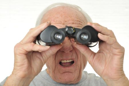 Man with binoculars is confused on how to use them. Stock Photo