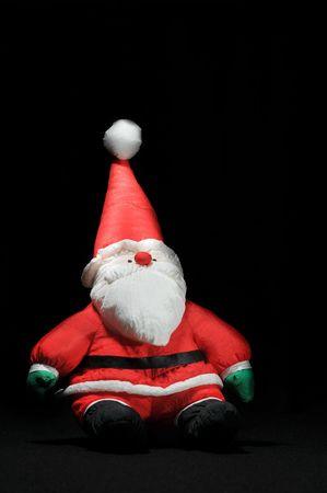 Santa Claus on black surface sitting up straight.