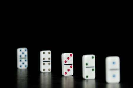 Dominoes from two to ten stand on a black background. Focus on the three and three domino. Stock Photo
