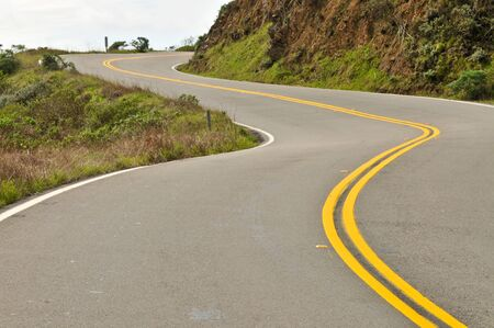 curving lines: Double yellow lines follow a curving road Stock Photo