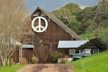A barn at the end of a road with a peace sign photo