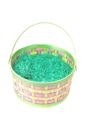Easter basket sits empty with green grass on white