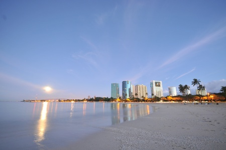 Buildings and ocean with a full moon setting. Stock Photo - 8249493