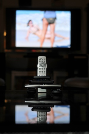 Remote controls for TV on a table in front of a large screen TV photo