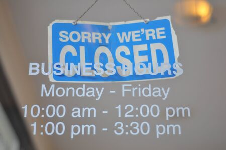 Business hours and a closed sign in a window