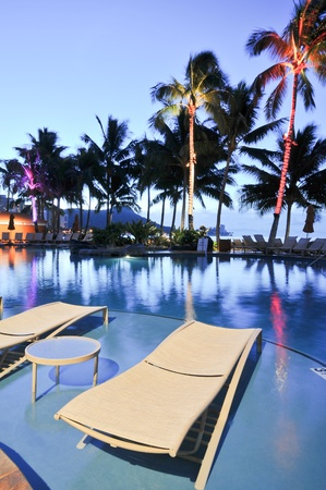 Palm trees reflect in a swimming pool at night time with lounge chairs. Stock Photo - 11571096