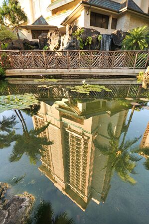 A hotel reflects from a pool with palm trees and a bridge Stock Photo - 11571100