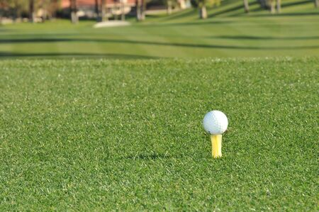A golf ball sits on a yellow tee ready to be hit down the fairway.