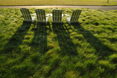 Three chairs sit in a grass field in the sun. Stock Photo