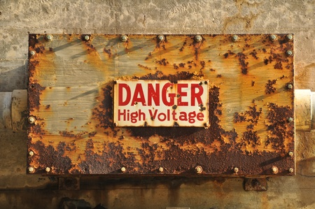 A wall with a rusty box with a Danger high voltage sign on it