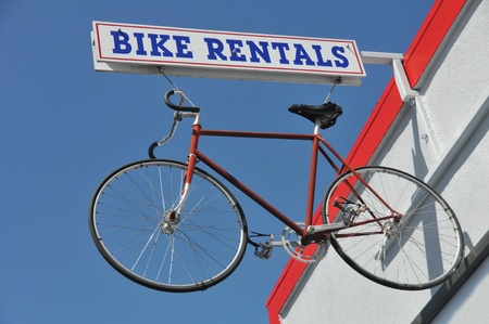 rentals: Bike rental sign with a bike haning from it next to a building