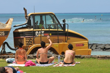 sun bathers: Beach goers wave at  the Waikiki Beach Maintenance Project driver which is restoring the beach to its mid-1980 Editorial