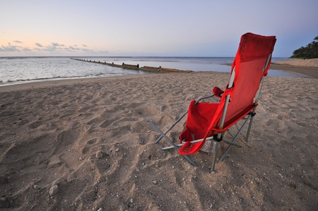 broken chair: An old broken chair sits on the sandy beach by the ocean.