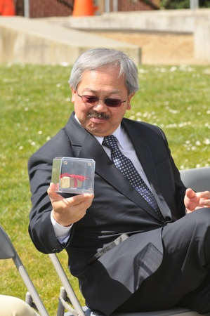 San Francisco, USA - May 4, 2012  San Francisco Mayor Ed Lee examines a piece of rebar that is a gift from the recently demolished Doyle Drive  The demolition is part of the Presidio Parkway project to rebuild the approach road to the Golden Gate Bridge f