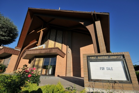 A Baptist church has a For Sale sign in front Stock Photo