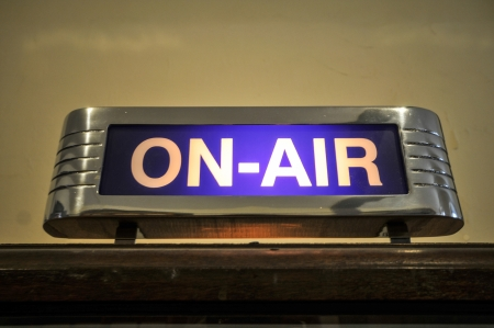 An old ON-AIR sign glows on above a studio door Stock Photo