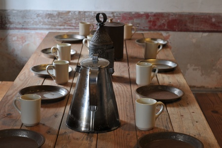 antique: An old fashioned wood table bench holds old tin plates and coffee mugs.