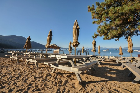 Bench tables with closed umbrellas on sand by lake shore  Stok Fotoğraf