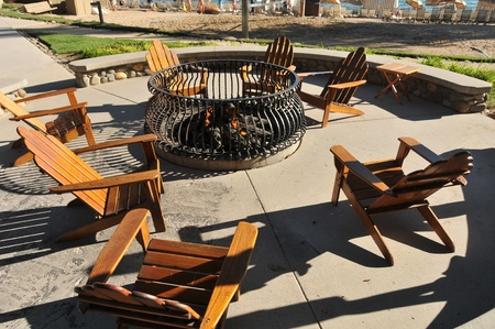 Many empty chairs surround a burning fire pit at the beach  photo