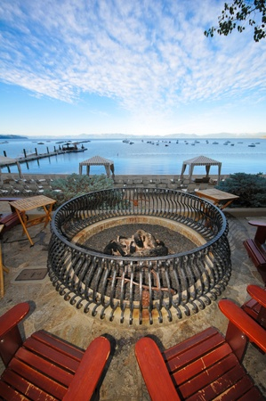 Fire pit with logs on the beach surrounded by adirondack chairs