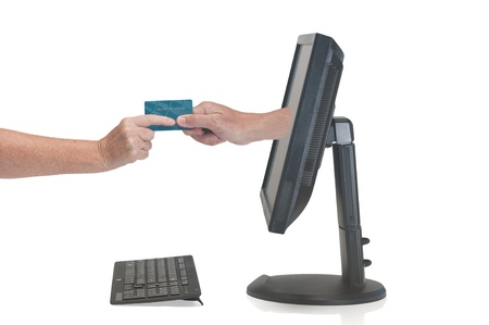 Hand coming out of a monitor screen grabs a credit card from the users hand Stock Photo - 15125818