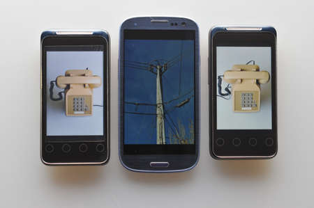 Three cell phones showing how phone calls were made in the past