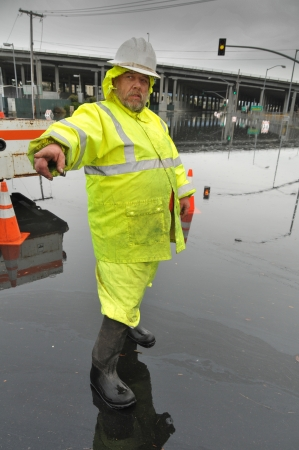 Worker in yellow rain outfit directs traffic from flood photo