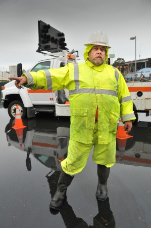 Worker in yellow rain outfit directs traffic from flood with trunk in background photo