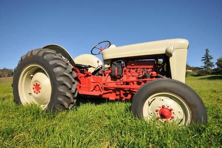 An old antique tractor in a field of long grass