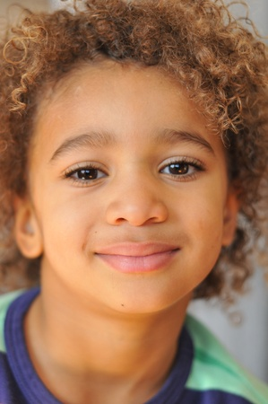 Curly hair mixed race boy posing for portrait Stock Photo