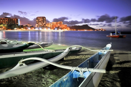 Night scene of a group of outrigger conoes on the beach with Diamond Head Stock Photo